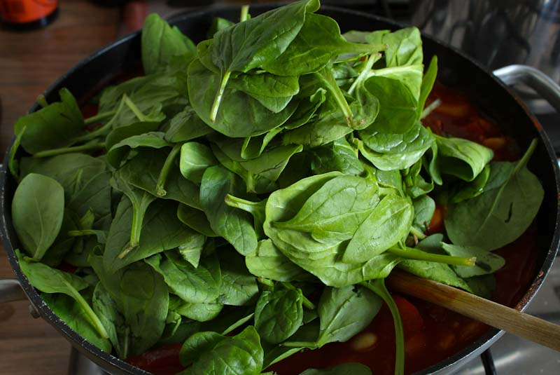 Spinach Being Added to Butter Bean Stew