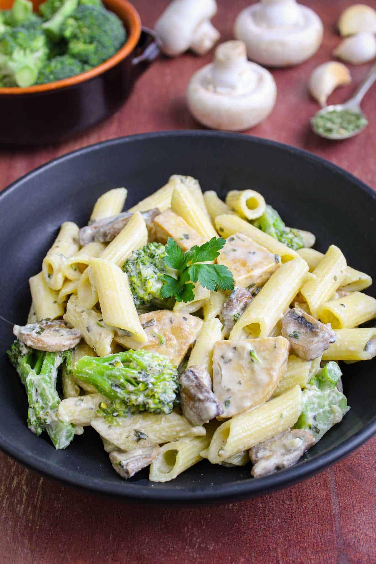 Bowl of Creamy Vegan Pasta with Tempeh, Broccoli, and Mushrooms