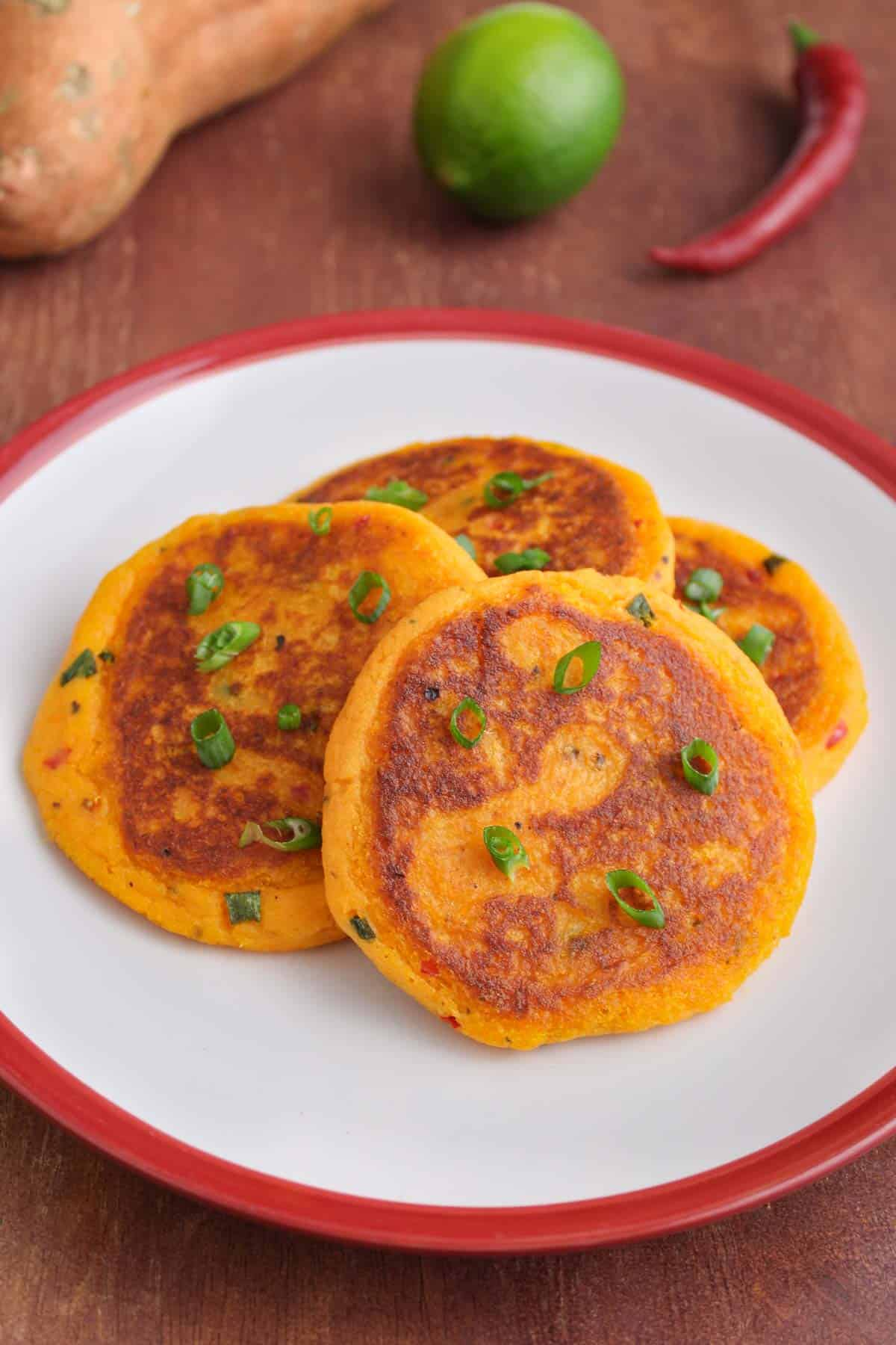 Sweet Potato Cakes on Plate with Chopped Spring Onion